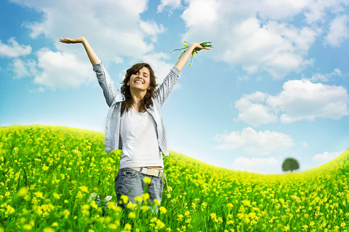 Abbotsford woman throwing hands up in joy while standing in a field