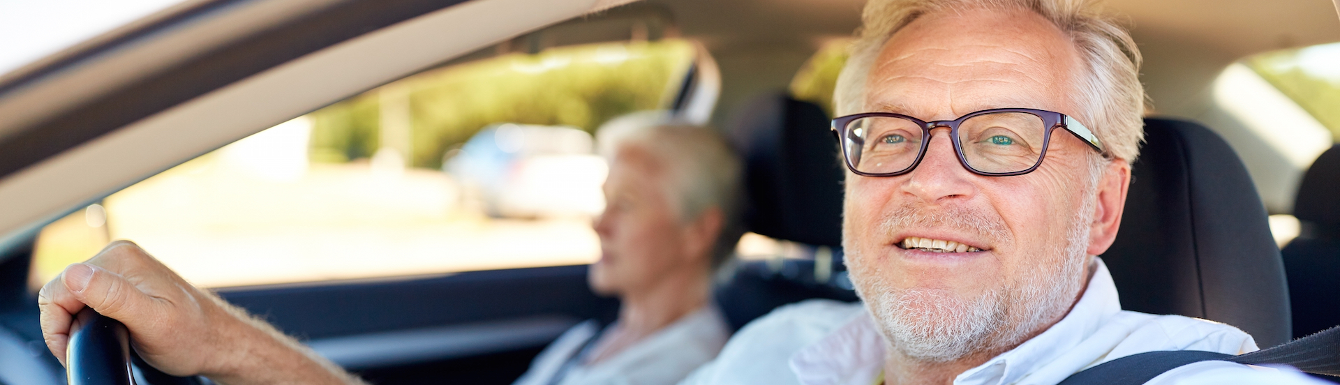 road trip, travel and old people concept – happy senior couple driving in car