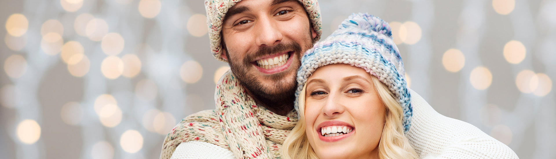 winter, fashion, couple, christmas and people concept – smiling man and woman in hats and scarf hugg